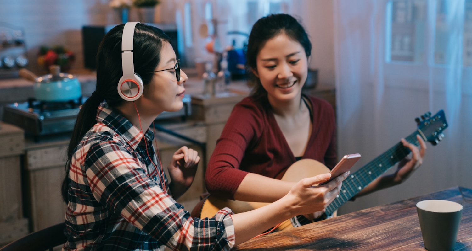 two asian japanese ladies friends sitting at wooden modern kitchen at home in midnight with guitar. young girl reading sheet music on cellphone. woman in headphones holding mobile phone enjoy melody